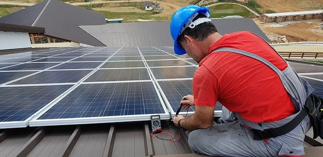 Solar system technician checking solar panels.
